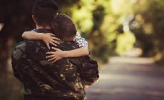 boy hugging dad in army uniform