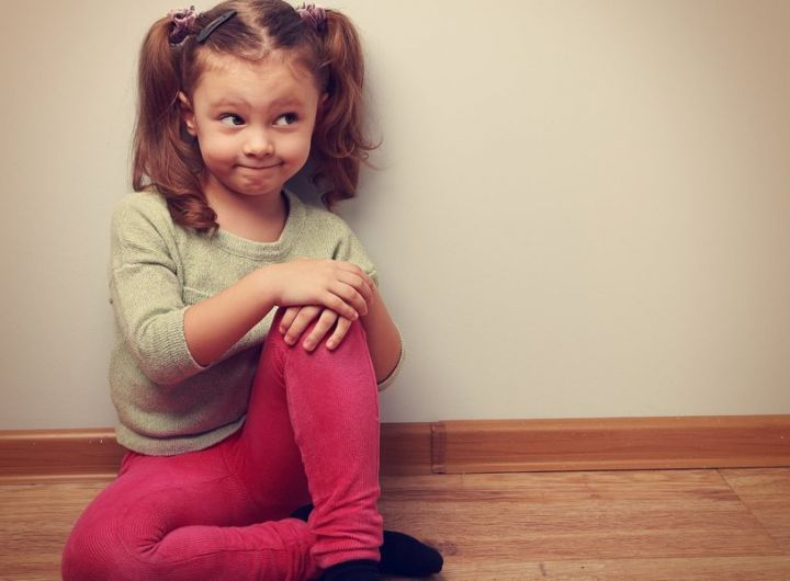 bemused little girl sitting on the floor