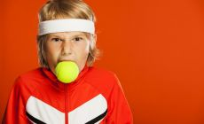 boy in tennis gear with tennis ball in his mouth and angry expression